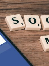 a phone with the facebook login open on the screen next to a scrabble letters spelling out social media