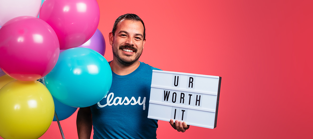 man with a classy t-shirt holding a sign that says ur worth it