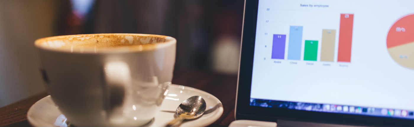 a cup of coffee on a plate with a spoon next to an open laptop with charts