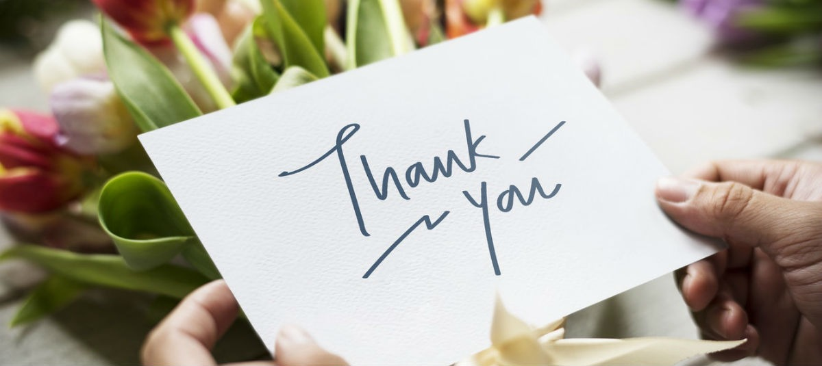 hands holding a thank you note in front of a bouquet of flowers