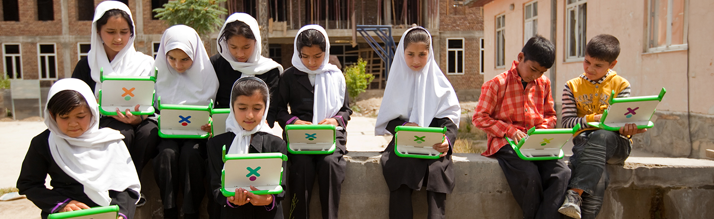 young girls with white head scarves working on small green computers