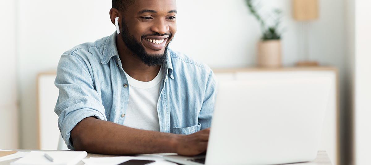 man in blue smiling and typing on laptop