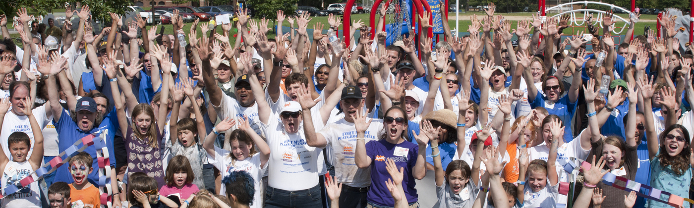 large group of volunteers posing together and raising their hands