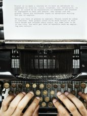 hands typing on a typewriter with a cup of coffee