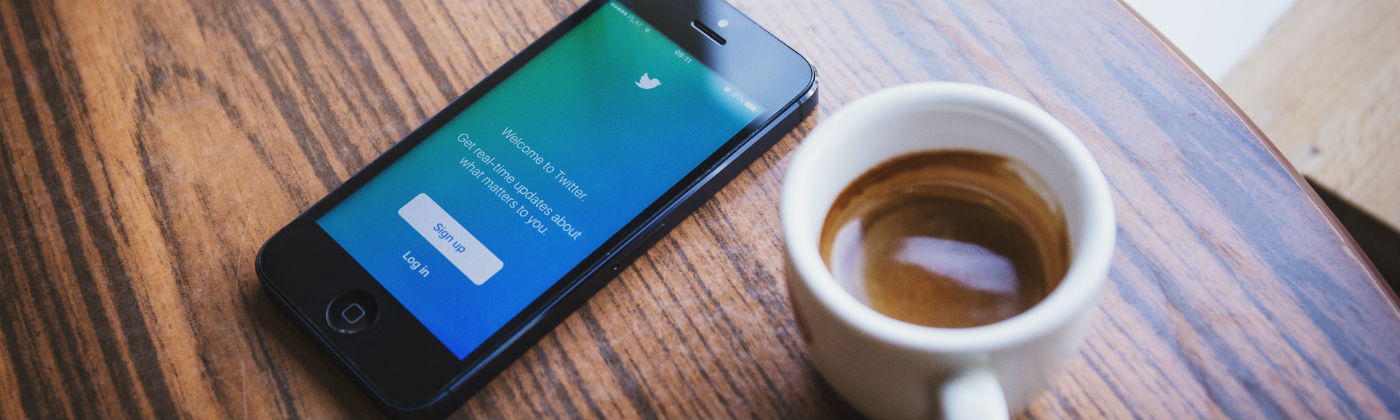 an espresso and a mobile phone with twitter logging on a table