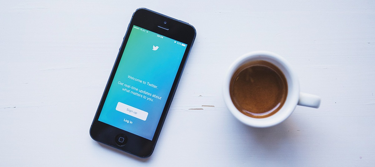 phone open to twitter next to a cup of coffee