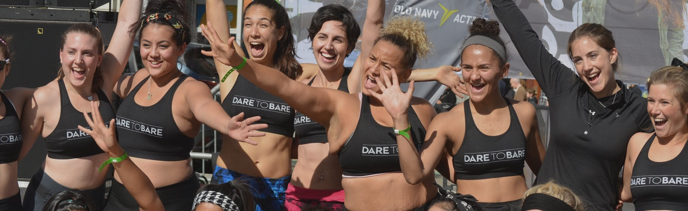 women in Dare to Bare sports bras celebrating and embracing at a Dare to Bare fundraising event