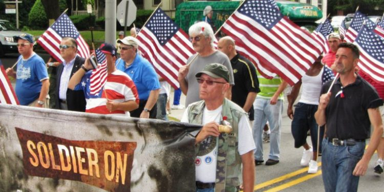 Image of men in a parade with American flags marching for Soldier On.