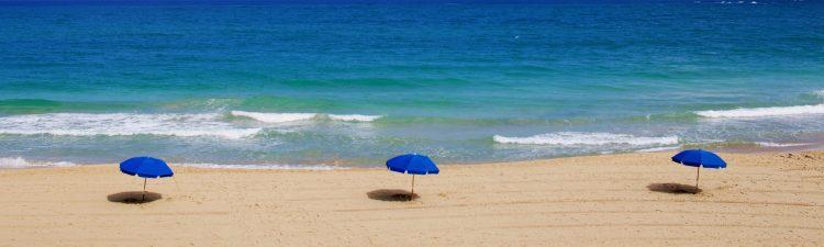 Image of beach with three umbrellas.