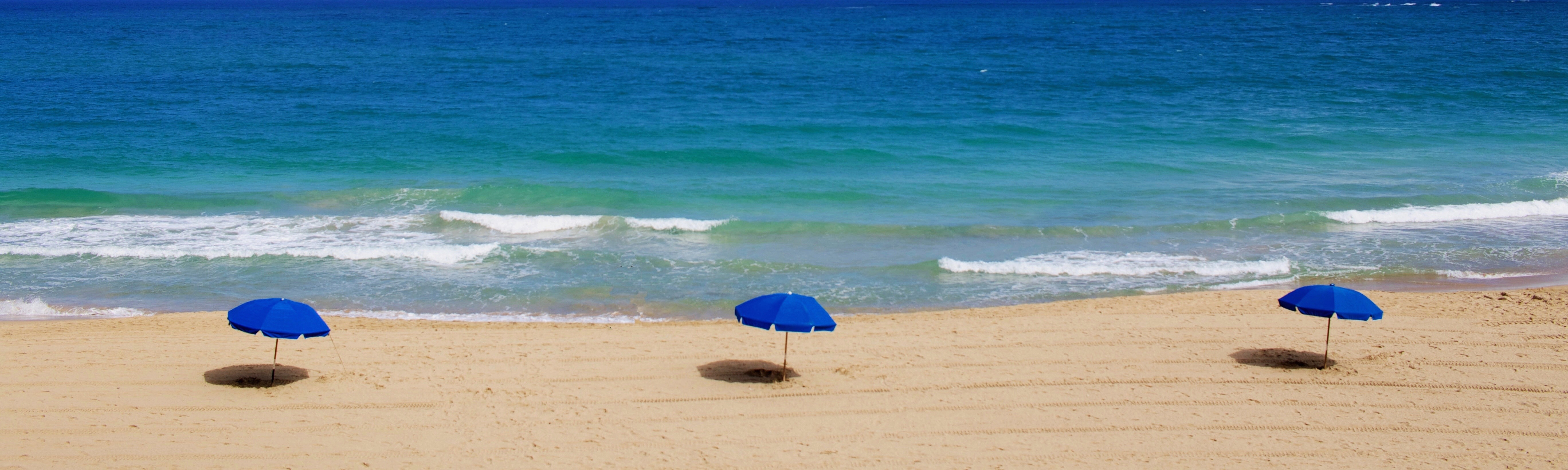 Image of beach with three umbrellas.