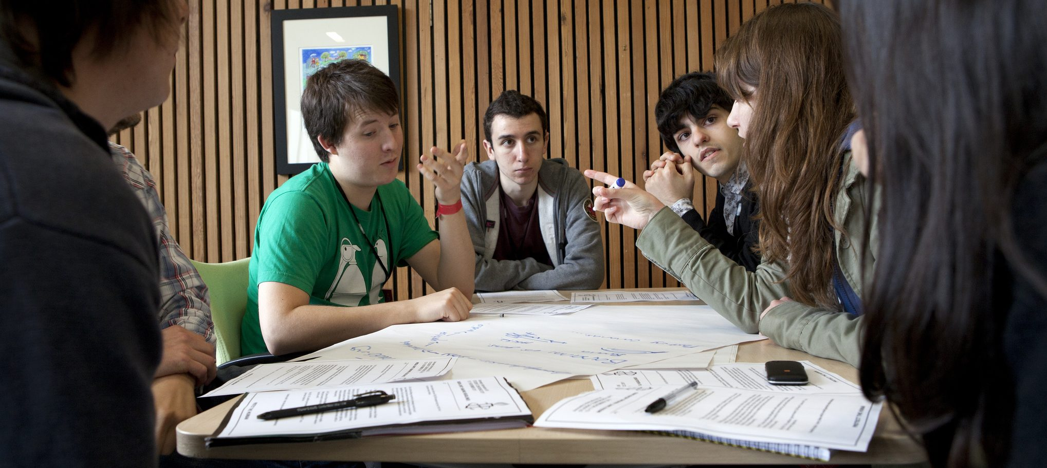 group of students talking over a table with papers and pens around