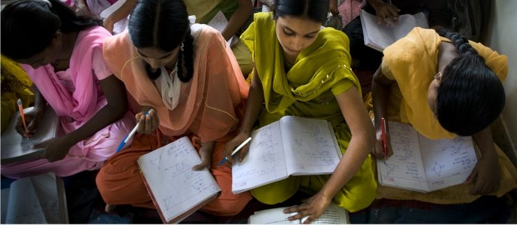 young girls in colorful outfits writing in notebooks