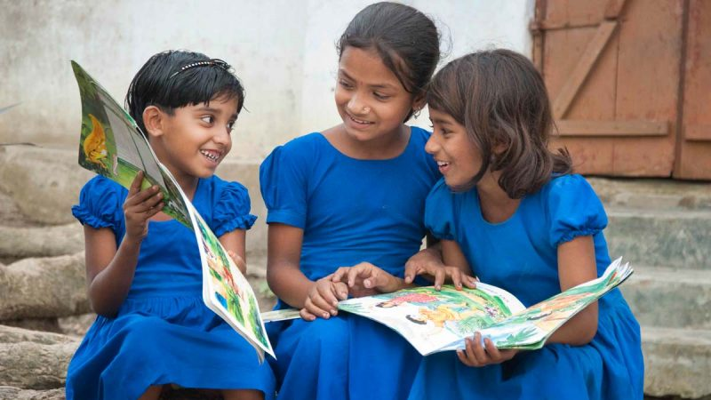 three young girls in blue dresses reading magazines together