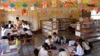 students in a classroom with drawings hanging on the walls and from the ceilings