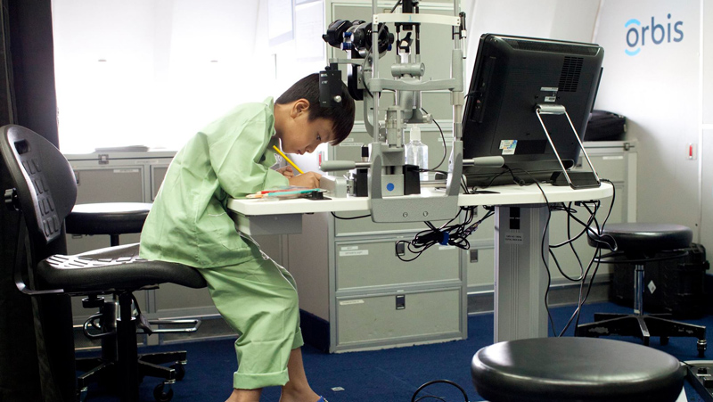 young boy in a green hospital gown writing on a paper in an eye doctor's office with equipment