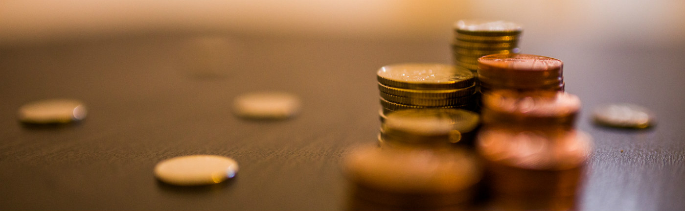 close up of stacks of coins sitting on a desk
