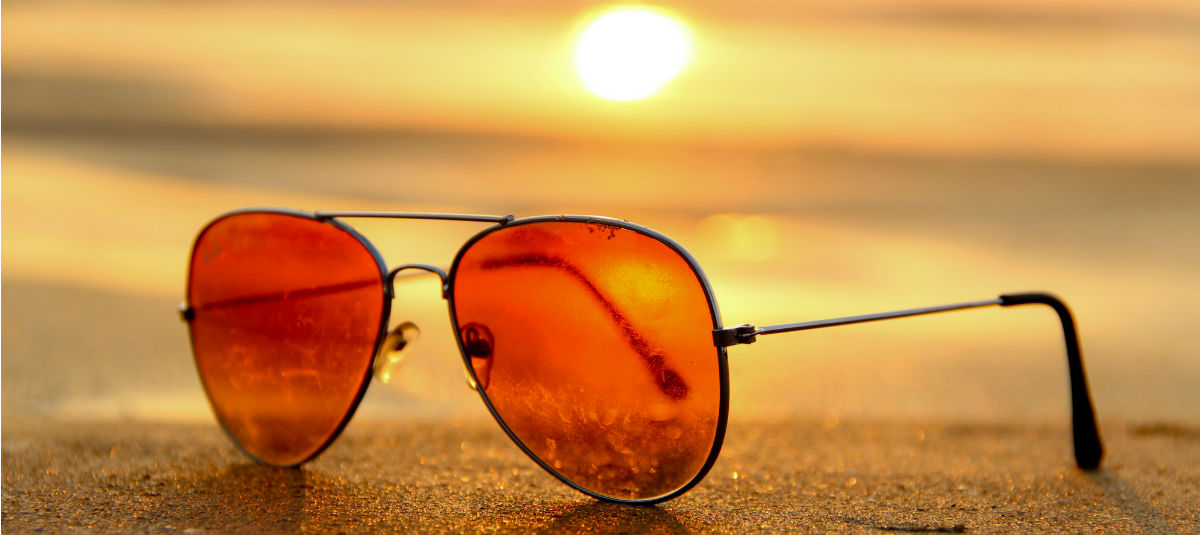 sunglasses with orange lenses sitting on the beach
