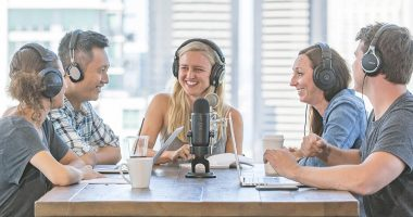 group of people sitting around the table with microphones wearing headphones