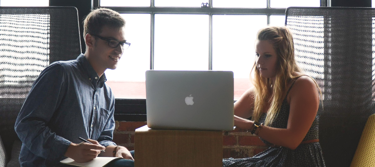 two people collaborating on a laptop in front of a window