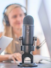 blonde woman wearing headphones and speaking into a microphone
