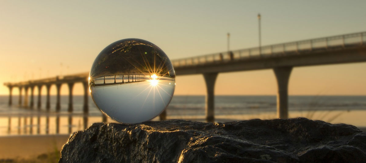 glass ball on a cliff at the beach with a bridge in the background