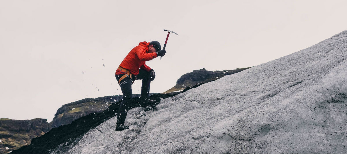 man in a red jacket climbing a mountain raising an ice pick