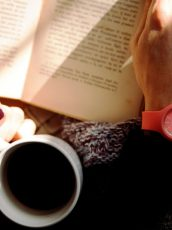 Person drinking coffee while reading a book