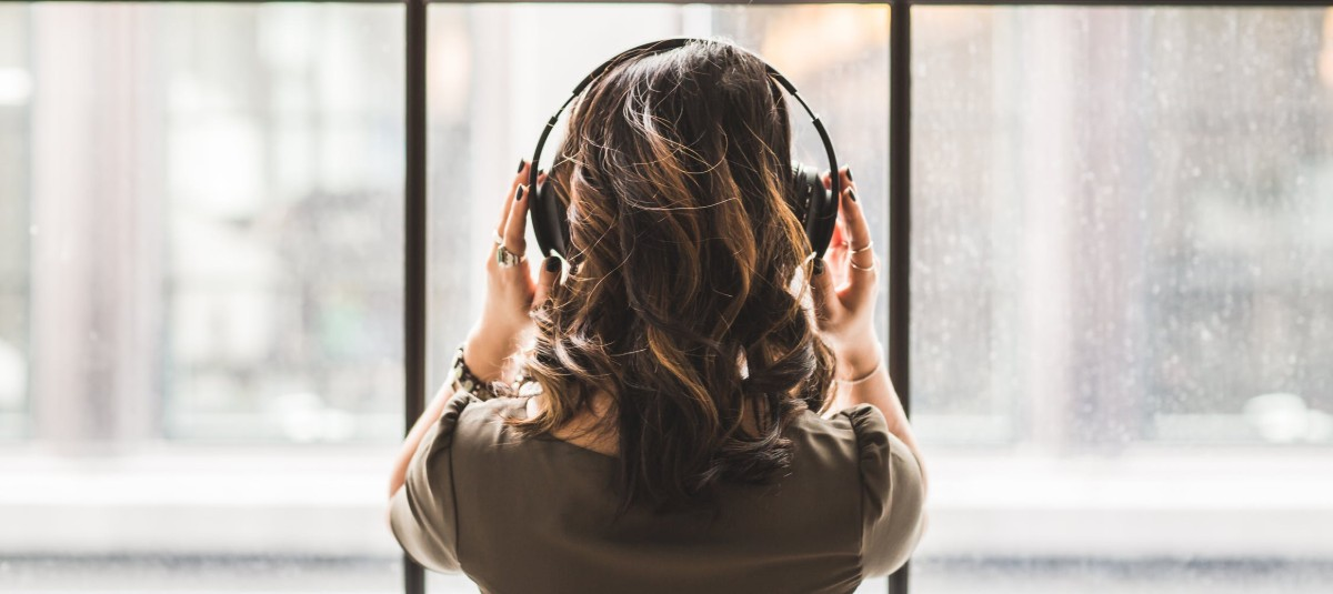 a woman with brown hair standing in front of a window and listening to a pair of headphones