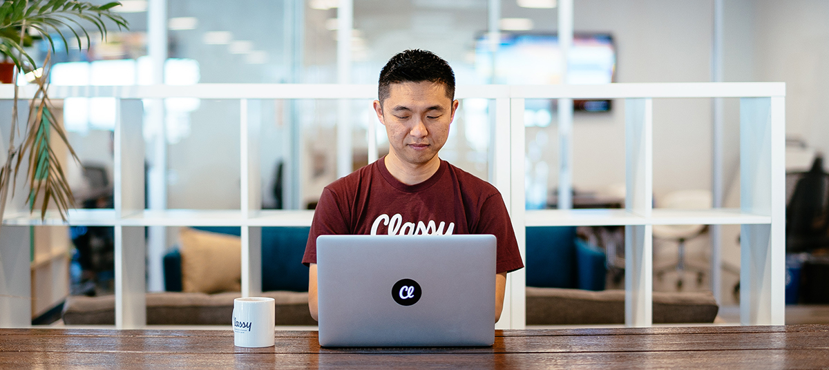 employee wearing a maroon Classy t-shirt and working on a laptop computer