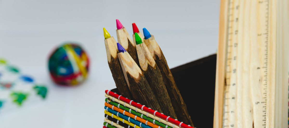 close up of different colored pencils and a wooden ruler