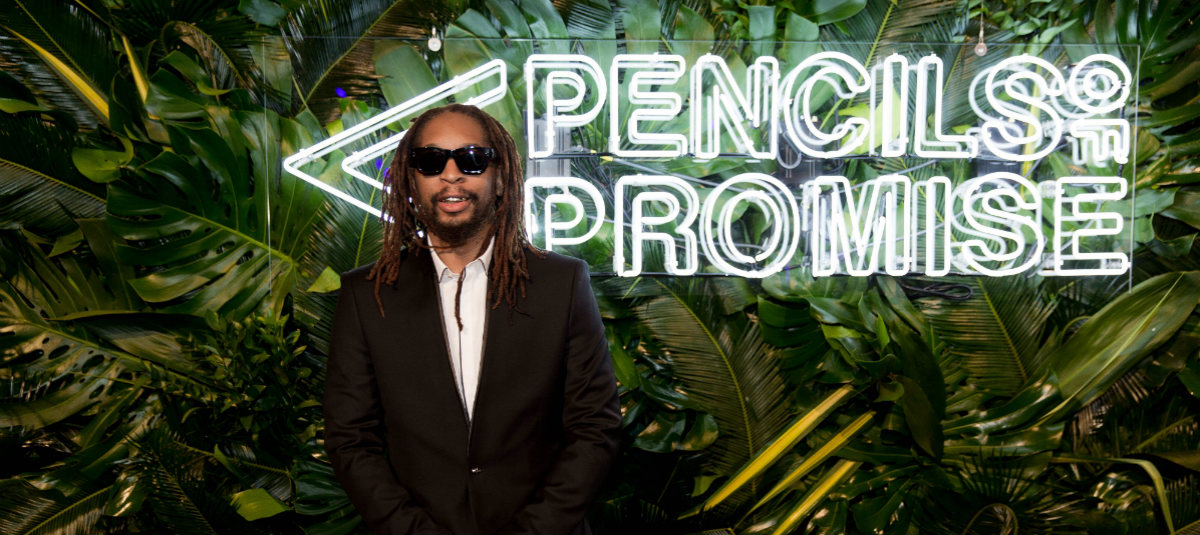 Celebrity Lil Jon posing in front of a Pencils of Promise sign with foliage