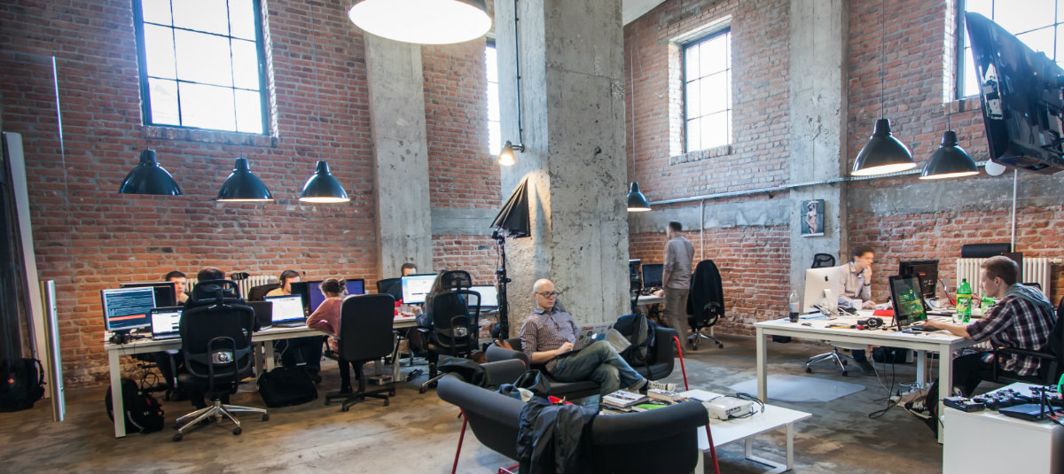 Classy office with desks and couches where people are working and red brick walls
