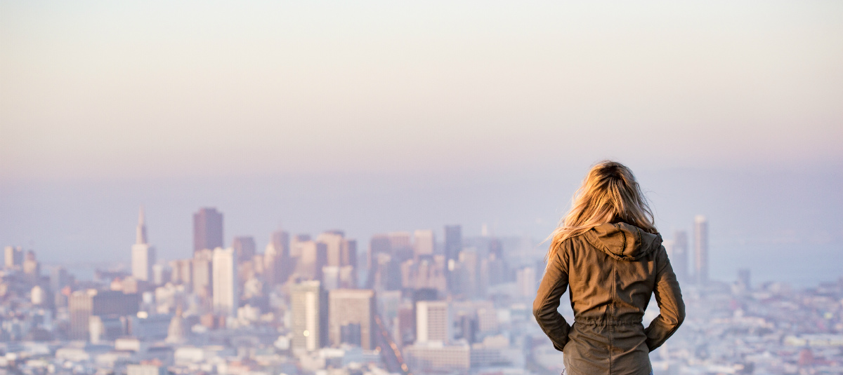 woman with blonde hair looking out over a cityscape