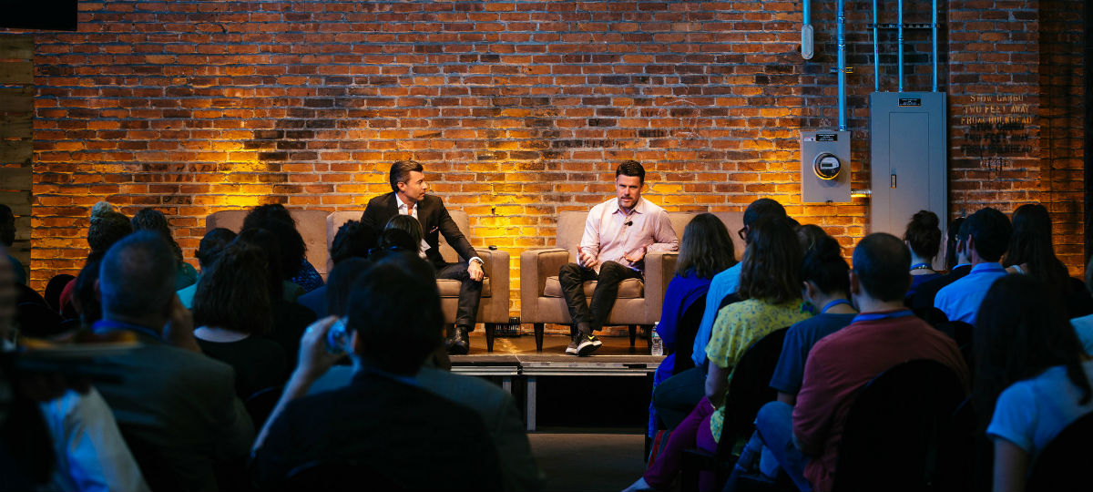 two speakers sitting onstage in front of a crowd at the Collaborative
