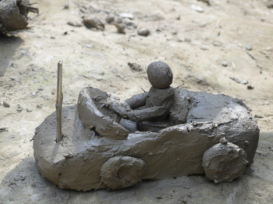 A child's toy car is fashioned from mud.