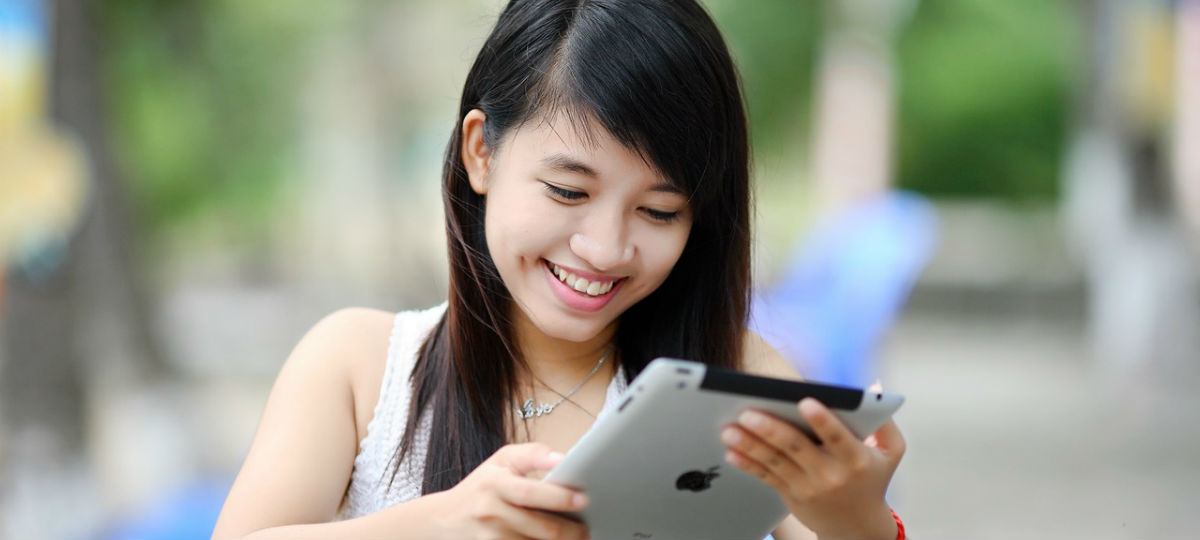 girl with dark hair smiling and looking down at an ipad screen