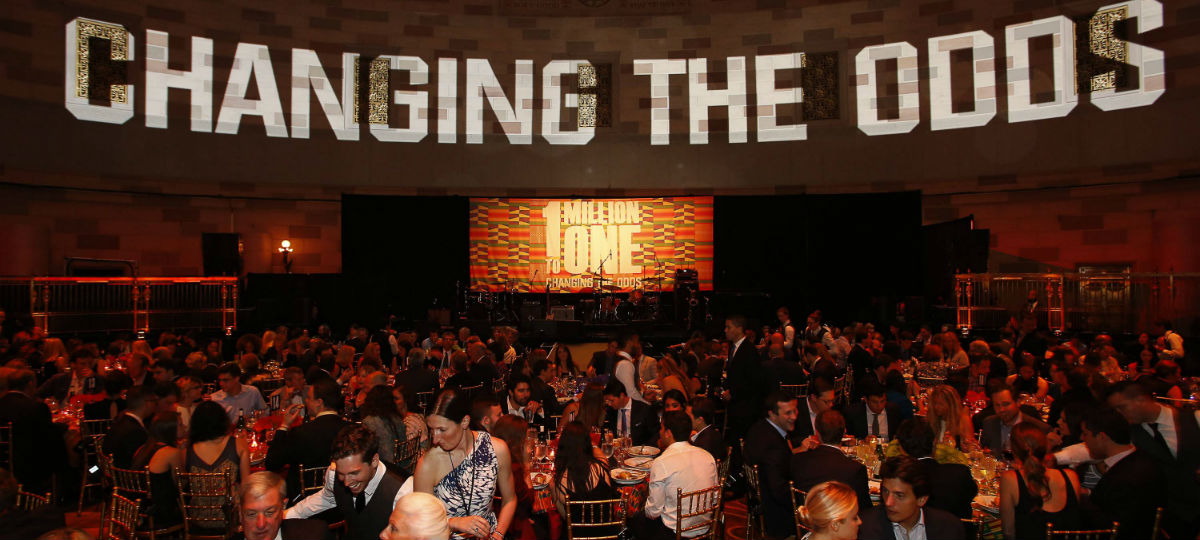 ubuntu fundraising gala with a sign saying changing the odds and a lot of guests