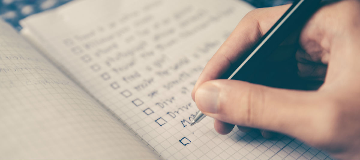 person writing a checklist into a graphic notebook