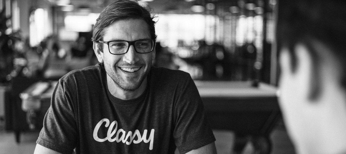 black and white man in a classy t-shirt with glasses smiling and talking