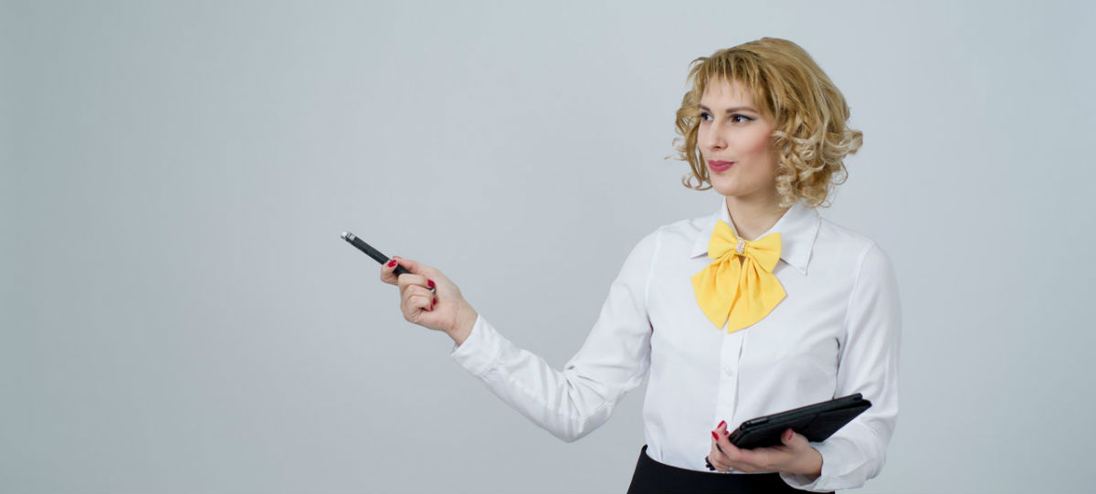 blonde woman giving a presentation wearing a white button up and a large yellow bow and pointing with a pen