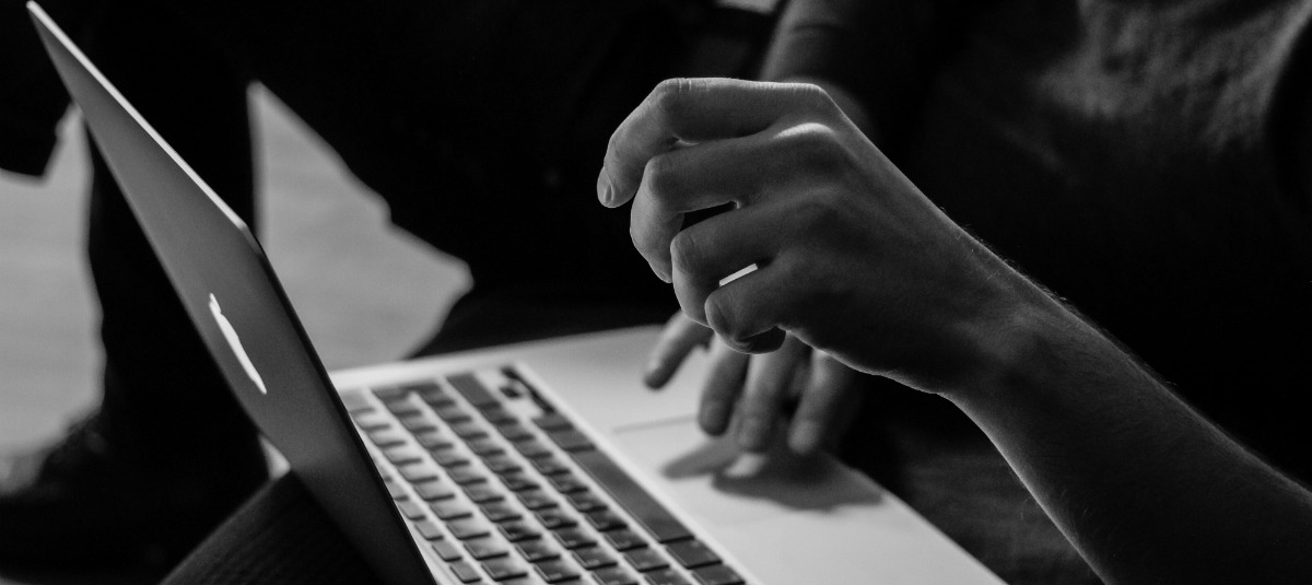 black and white photo of hands typing on a laptop