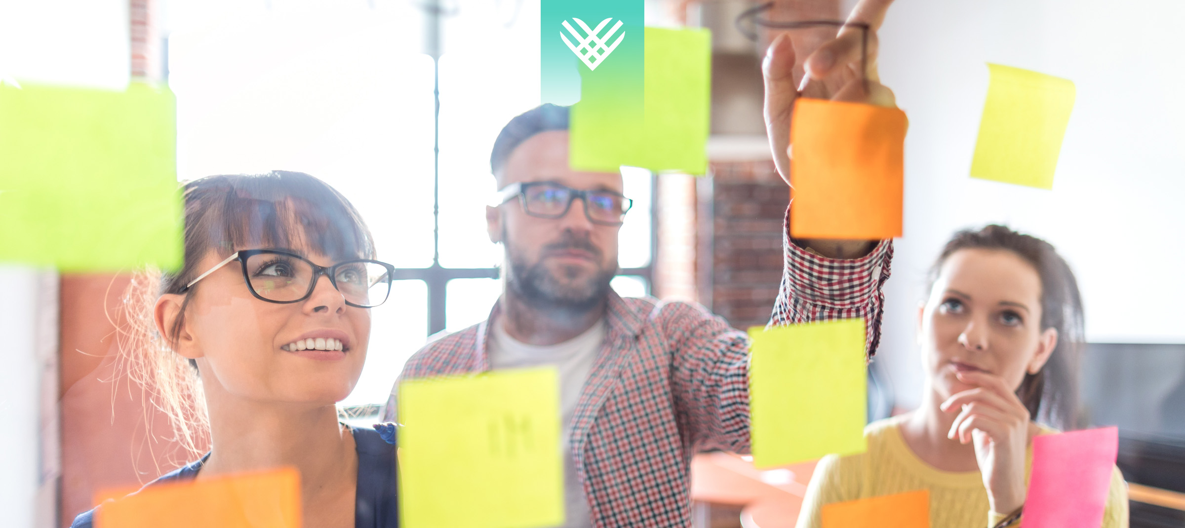 people collaborating and looking at a board with post it notes Giving Tuesday fundraising ideas
