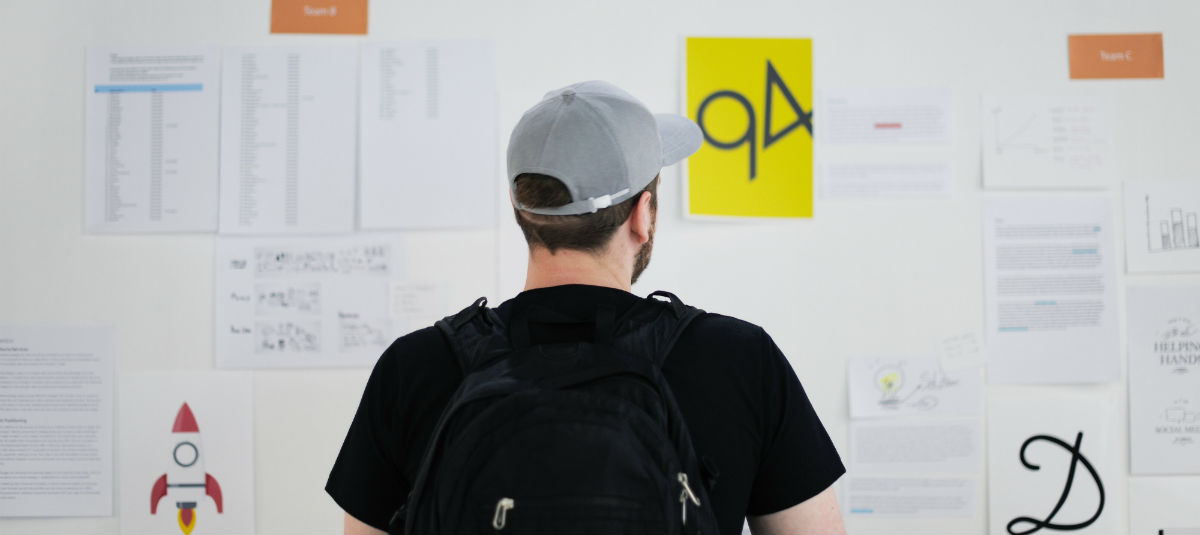 guy with a black backpack and a grey hat looking at a wall with papers on it