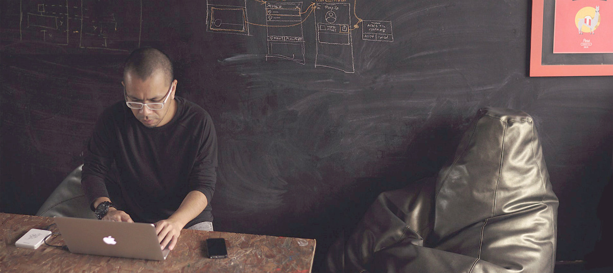 man working on a computer in front of a chalkboard wall with writing