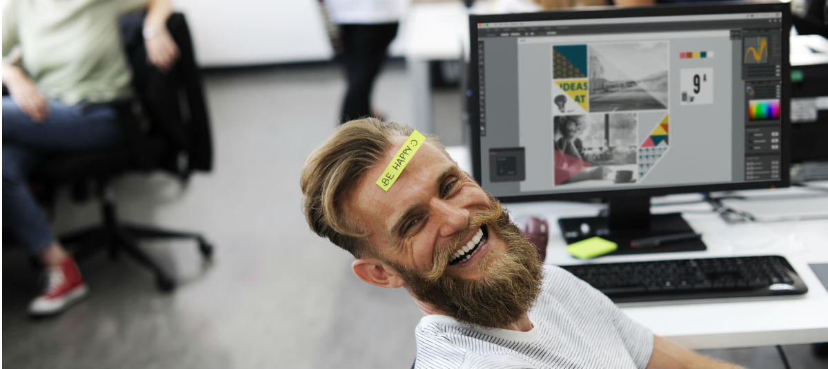 man sitting at a desk with a computer smiling with a note on his head saying be happy