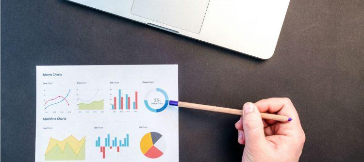 Image of hand holding pencil examining charts