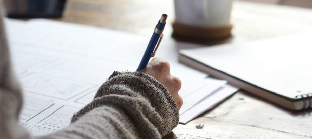 person writing on paper with a pencil
