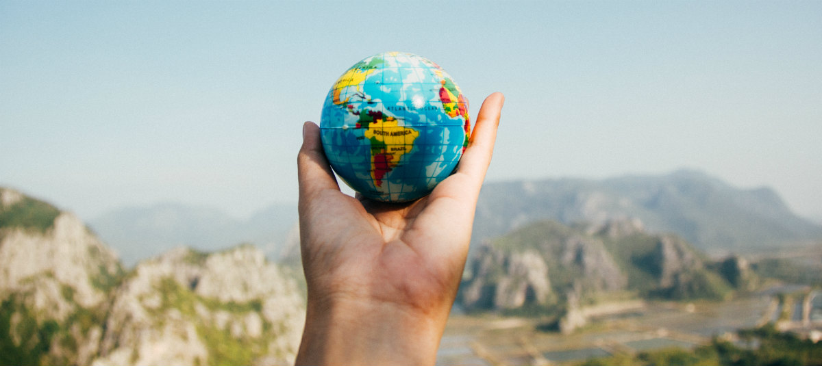 hand holding a mini globe in front of a mountain range