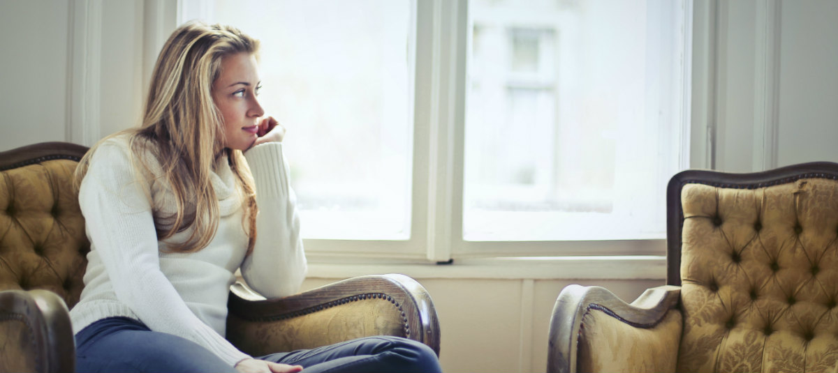 woman in a blond sweater sitting in a chair and looking out of the window