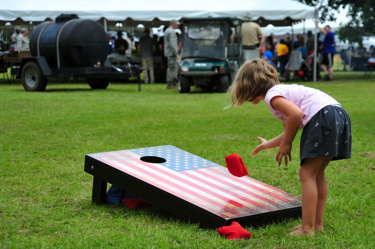 child playing cornhole event